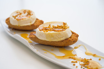 Fresh goat cheese with honey and pollen on the bread, macro, isolated