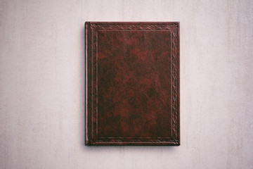 the book in a red cover on a light gray background, top view