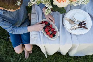 Junge sitzt barfuß  im Garten am Tisch und isst Erdbeeren