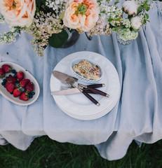 Kuchen und Erdbeeren auf dem Gartentisch mit Blumendekoration