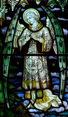 Fototapete - Angel with folded hands in stained glass