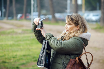 Adult woman taking pictures in the nature