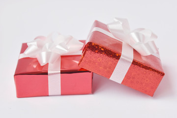 Red gift box and ribbon bow on white background. Concept for Valentine day, Christmas present and New Year.