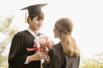 Couple young asian graduate holding certificate in hand happyness with girlfreind in Commencement day.