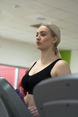 A beautiful young woman exercising on a treadmill at the gym