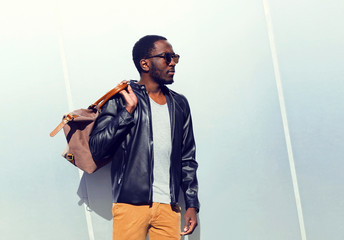Wall Mural - Fashion portrait confident african man with a bag in the city on a copy space empty grey background
