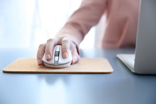 Woman using computer mouse with laptop on table