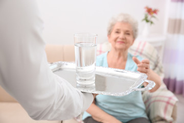 Young man serving glass of water for elderly woman. Concept of nursing