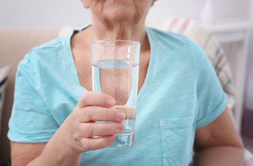 Elderly woman holding glass of water, closeup. Concept of retirement