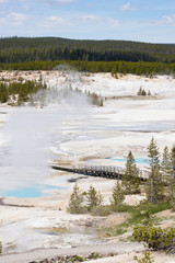 Porcelain Basin Yellowstone National Park with erupting geysers and brilliant blue thermal pools photographed from above. A boardwalk skirts the thermal area.