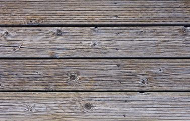 Close up of planks of wood in a boardwalk. The boards have a rough texture.