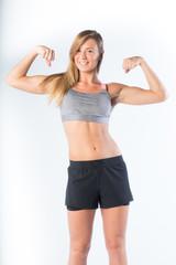 giovane ragazza bionda con fisico sportivo fa ginastica in  studio su fondale bianco