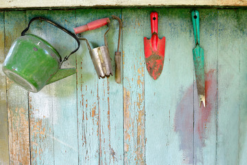 Old dirty farm gardening tools, spade, fork and rake on wooden wall