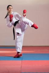 Woman In White Kimono And Black Belt Training Karate