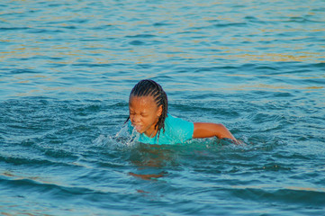 Young girl coming from under the water swimming