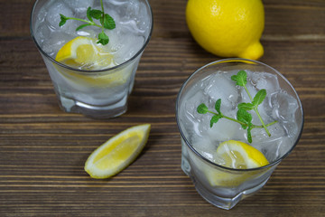 Refreshing beverage with lemon, ice and mint leaves in glasses, isolated on wooden background