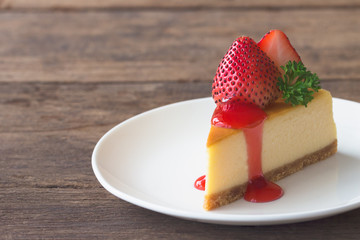 Homemade New York cheesecake on white plate decorated by strawberry,parsley and strawberry sauce. Moist and smooth classic baked cheesecake. Copy space background of delicious New York cheesecake.