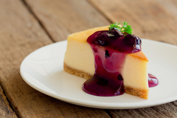 Homemade blueberry cheesecake on white plate decorated with parsley and blueberry sauce. Moist and smooth classic baked cheesecake. Copy space background of delicious blueberry New York cheesecake.