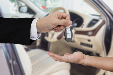 Hand giving and receiving car key remote, with modern car backgrounds