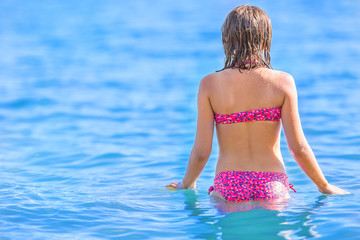 Young girl standing in the sea before swimming.