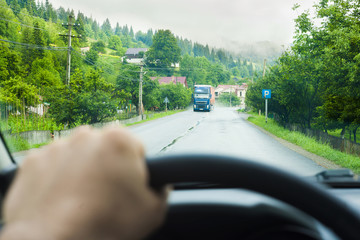 view of road and hand on wheel of car driving, focus on background