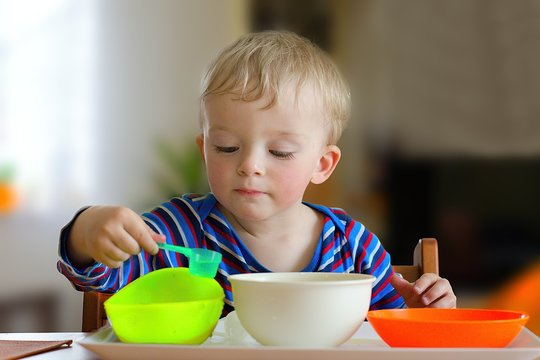 Toddler playing with water bowl activity