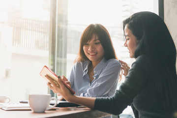 One-on-one meeting.Two young business women sitting at table in cafe. Girl shows colleague information on laptop screen. Girl using smartphone blogging. Teamwork business meeting. Freelancers working.