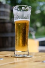 Glass full of beer with white foam on wooden table