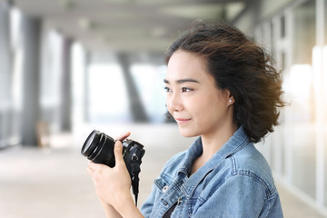 Young beautiful woman chilling out with camera in hand on balcony building