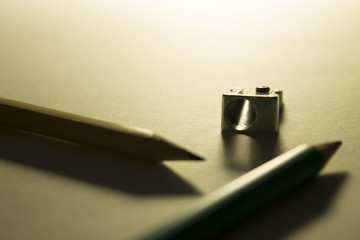 Two pencils and a pencil sharpener on the paper in the backlight