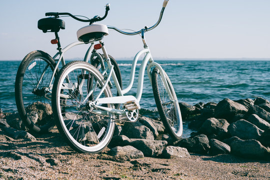 Two retro bike on the beach against the blue sea