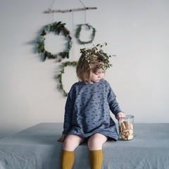 Kleines Mädchen mit Kranz auf dem Kopf nascht Kekse zu Weihnachten