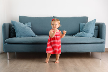toddler girl dancing by the couch