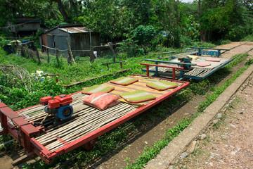 Rice fields - bunte Wägen fahren auf Gleisen durch Reisfelder in Kambodscha