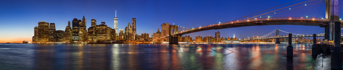 Wall Mural - Panoramic view of Lower Manhattan Financial District skyscrapers at twilight with the Brooklyn Bridge and the East River. New York City