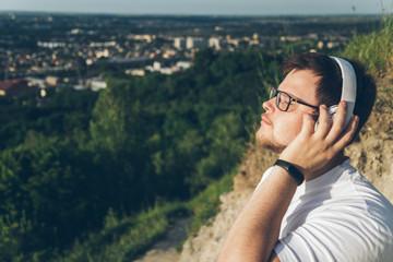 man listen music on the peak of the hill