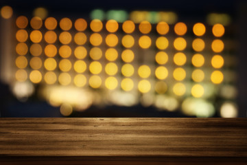 wooden table in front of night bokeh hotel. Ready for product display montages