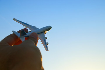 close up of man's hand holding toy airplane against sunset sky