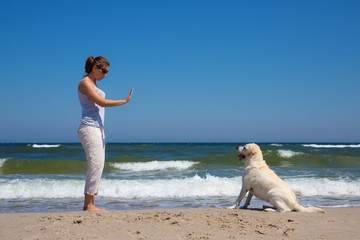 Woman training a dog on the beach