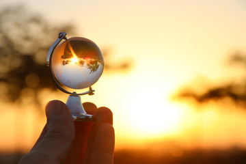 male hand holding small crystal globe in front of sunset