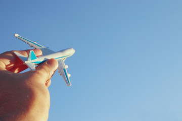 close up of man's hand holding toy airplane against blue sky