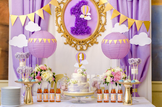 Interior decoration for a child's birthday is one year in purple colors. Candy, macaroon, tiered cake, and juices.