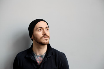 Portrait of stylish fashionable young European male with facial hair and tattoo on chest looking up, having dreamy inspired expression, dressed in black clothing. People and lifestyle concept