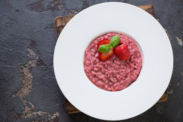 Above view of a white plate with strawberry risotto on a brown stone background, horizontal shot