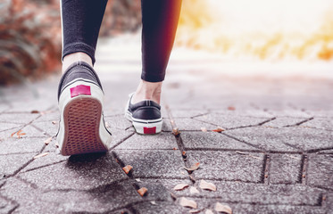 Runner feet running in the park closeup on shoe.