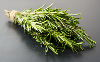 Sprigs of rosemary tied with string on a dark gray background.