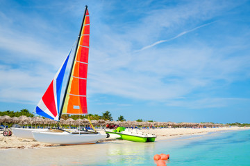 Wall Mural - The beautiful Varadero beach in Cuba with a colorful sailboat