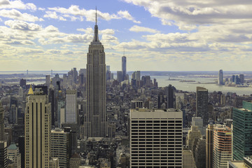 View of the Empire State Building  and lower Manhattan as seen from the Rockefeller Center. Afternoon, cloudy skies