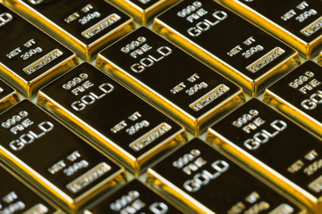 closed up shot stack of shiny gold bars as business or financial investment and wealth concept