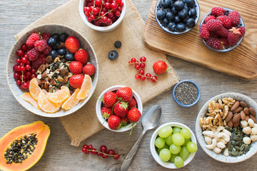 Paleo style breakfast, grain free muesli made with nuts and dried fruits, served with fresh berries, top view, selective focus
